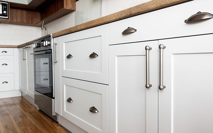 Beautiful white kitchen sink cabinet, seen from the exterior, with modern pulls and wooden floor