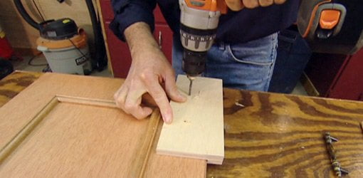 Drilling holes for handles in a cabinet door with homemade drilling jig