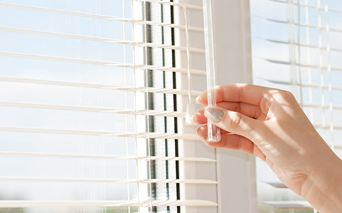 Woman with well-manicured and polished fingernails adjusts her window blinds to block out the sun