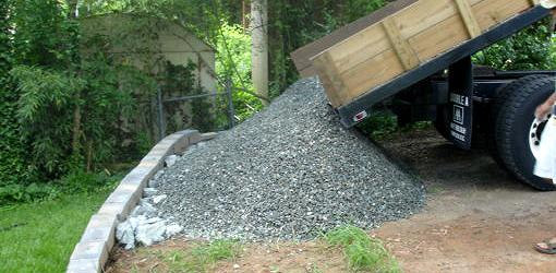 Dump truck dumping gravel in a yard