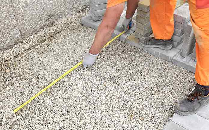 Construction worker measuring cubic yards for pea gravel