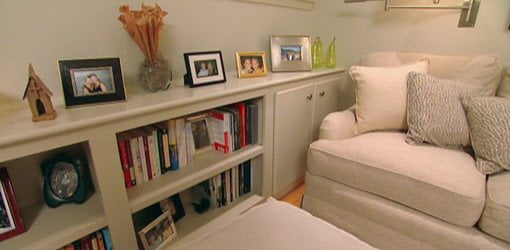 Small room with bookcase and sofa all painted beige color.