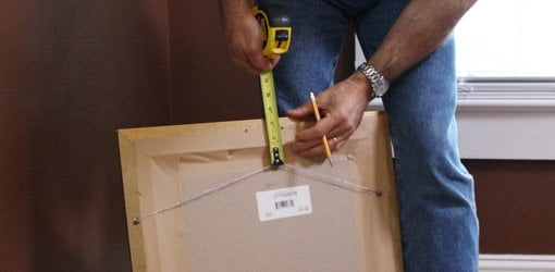 Measuring a picture from from the wire to the top with a tape measure.