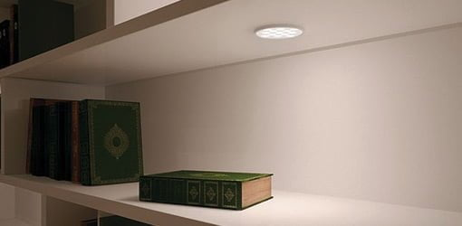 Häfele's Loox 12V Puck Down Light mounted in shelf on bookcase