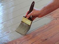 Applying paint to floor with paintbrush