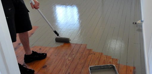 Painting wood floor with a roller.
