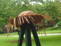 Hat on wooden tripod.
