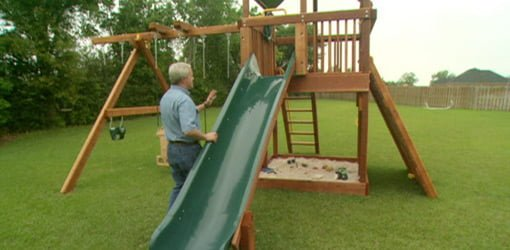 Danny Lipford with wooden play set in backyard.