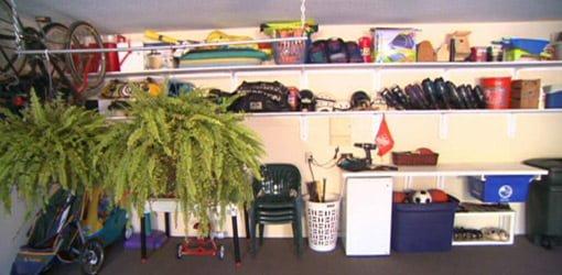 Organized garage after adding shelving, hanging plant racks, and bike hooks.