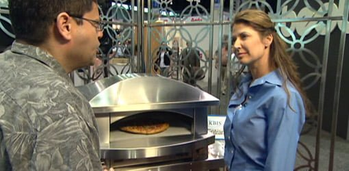 Jodi Marks examines outdoor gas pizza oven.