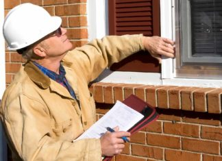 Home inspector checking windows on the outside of home and making notes on his clipboard.
