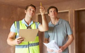 Young home buyer accompanies home inspector during inspection