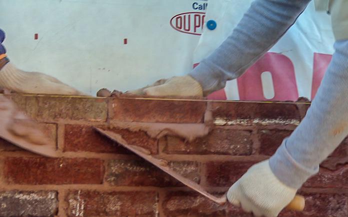 Man applies mortar while installing brick wall
