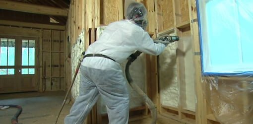 Spraying foam insulation in a the walls of a house under construction.