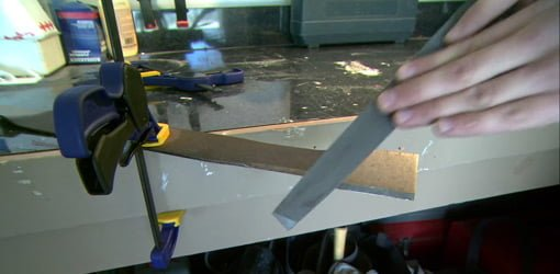 Sharpening a lawn mower blade with a file