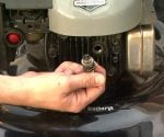 Removing spark plug from lawn mower.
