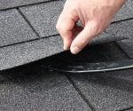 Lift a shingle on an asphalt roof with a flat prybar