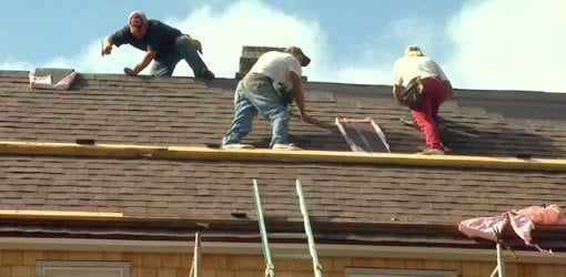 Workers repairing roof on home.