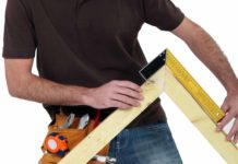 Contractor wearing a tool belt measures right angle