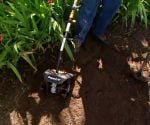 String trimmer tiller attachment being used to till up the rich soil in a garden.