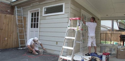 Painting fiber cement siding on exterior of carport conversion.