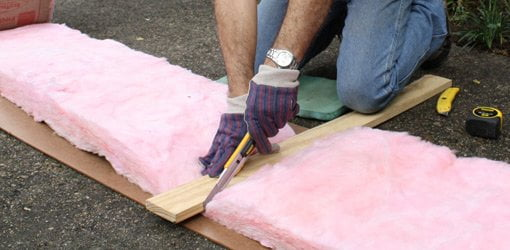 Using an extended blade utility knife to cut fiberglass insulation.