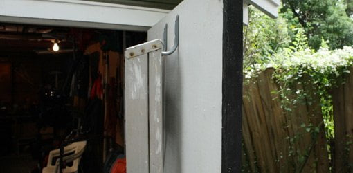 Stepladder hanging from hooks on shed door.