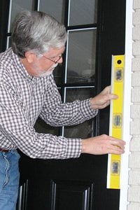 Checking door frame for plumb.