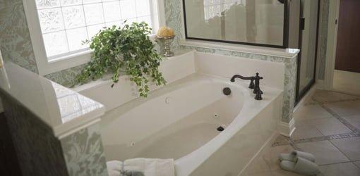 White built-in soaking tub under window.