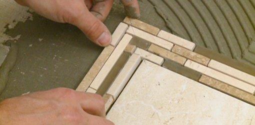Laying mosaic tile border on bathroom floor.