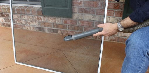 Cleaning window screens with a vacuum cleaner and upholstery brush attachment.
