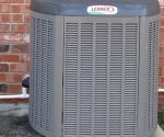 Lennox HVAC unit outside in front of brick wall.