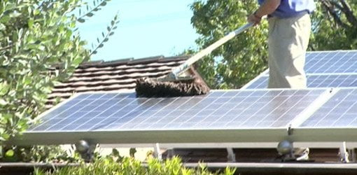 Solar panels on roof of house being cleaned with dust mop.