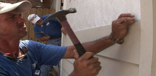 Installing fiber cement siding on a house.
