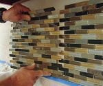 Installing a sheet of mosaic tile on a kitchen backsplash.
