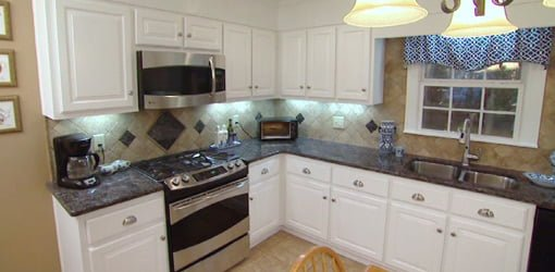 Completed kitchen after remodeling with new cabinet doors, appliances, and countertops.