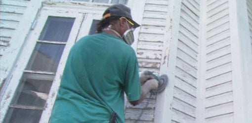 Using a rotary sander to remove old paint on the outside of a house.