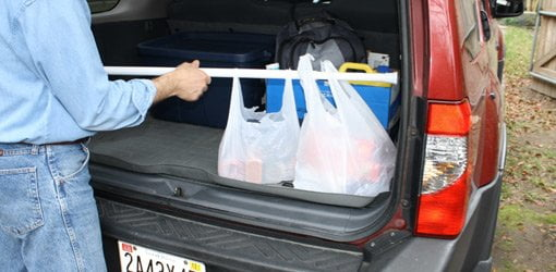 Expandable shower curtain rod being used to secure groceries in a car.
