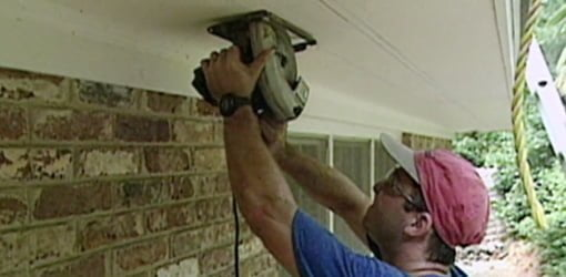 Using circular saw to cut soffit eave vent length.
