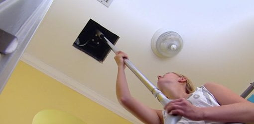 Using a vacuum cleaner crevice attachment to clean a bathroom vent fan.