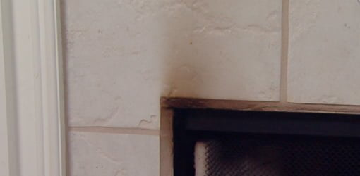 Black stains from soot and smoke on a wood burning fireplace surround.