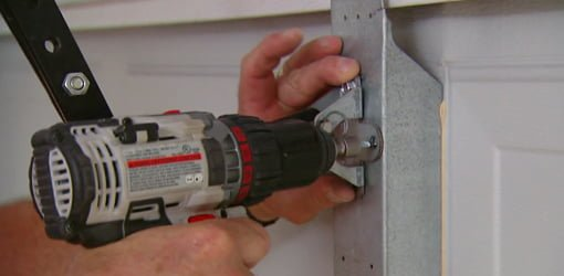 Using a drill to install self tapping sheet metal screws in a garage door opener bracket.