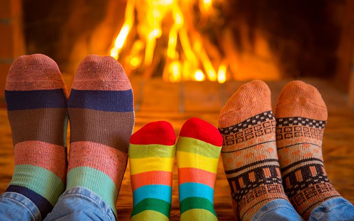 Close-up of three pairs of feet, mother, father and child, with warm socks, beside a wood-burning fire