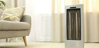 Electric space heater blowing warm air into stylish modern living room