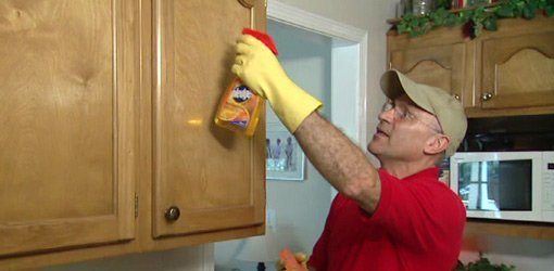 Using citrus cleaner and hot sponge to remove grease from kitchen cabinets.