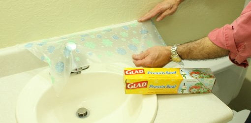 Applying plastic wrap to vanity backsplash.