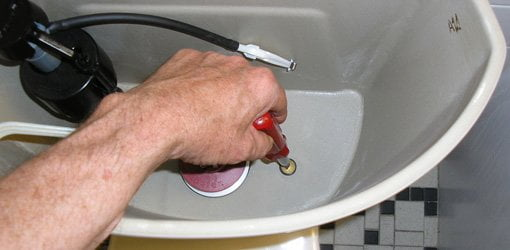 Using screwdriver to tighten bolt on toilet tank.