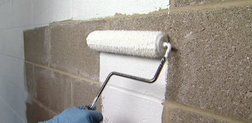 Rolling masonry waterproofer on concrete block basement wall.