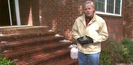 Danny Lipford by brick steps with pump up sprayer to apply chemical deicer.