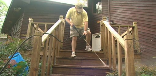 Cleaning deck steps with a pressure washer.